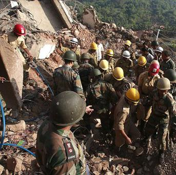 Indian Army soldiers and fire officials look for survivors from the debris of a building that collapsed in Canacona (AP)
