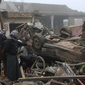 Civilians inspect the aftermath of a massive bomb attack in Balad Ruz, 45 miles north-east of Baghdad (AP)
