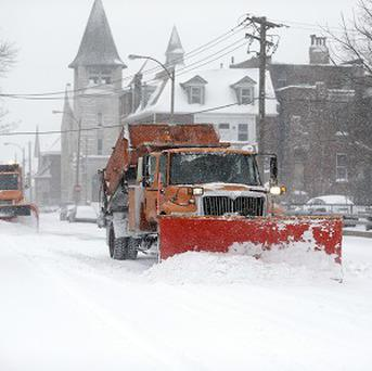 A convoy of snow ploughs attempt to clear the streets of St Louis (AP)