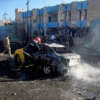 A firefighter hoses down a burned-out vehicle after a car bomb attack in Kirkuk (AP)