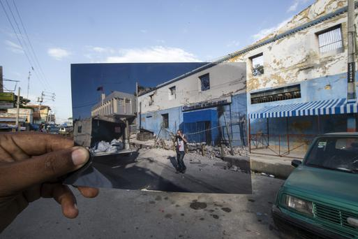 A old picture taken at the main prison of bodies in the back of pick up shortly after the Haiti earthquake is held up at the same spot in 2014. Photo: Mark Condren