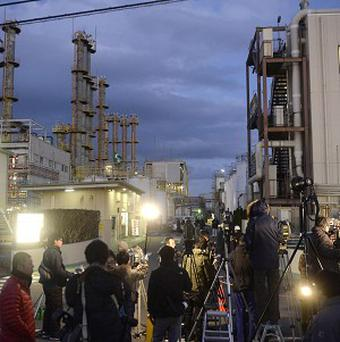 Local press gather at an entrance to the Mitsubishi Materials chemical factory following an explosion in Yokkaichi, central Japan. The explosion at the factory killed scores of workers and injured many others (AP/Kyodo)