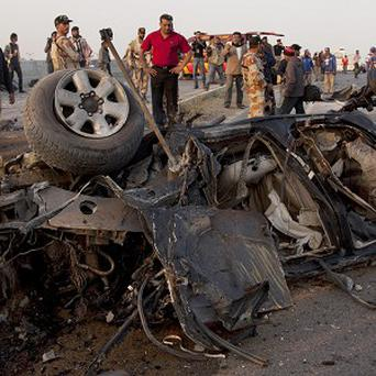 Pakistani investigators look at the vehicle destroyed in the bombing which killed Chaudhry Aslam (AP)