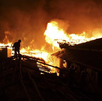 A firefighter works on a roof of a wooden building while a fire ravages the ancient town of Dukezong. (AP)