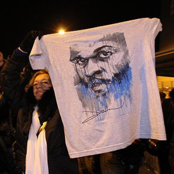 A fan of French comic Dieudonne Mbala Mbala hold up a t-shirt with his face on (AP)