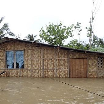 A house is half submerged following flooding of Compostela Valley and nearby provinces in southern Philippines (AP)