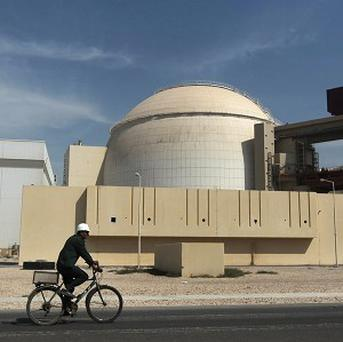 A worker cycles in front of the Bushehr nuclear power plant in Iran (AP)