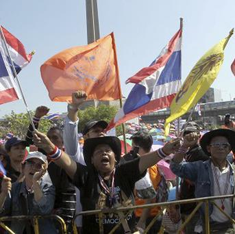 Anti-government protesters wave flags and chant slogans during a rally at the Victory Monument in Bangkok, Thailand (AP)