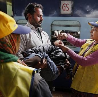 An Indian medical volunteer gives polio drops to a child at a railway station in Allahabad (AP)