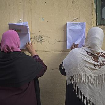 Women in Cairo search for their names on a polling list before casting their votes in the Egypt's constitutional referendum (AP)