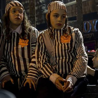 Orthodox Jewish children, wearing a Star of David patch and uniform similar to those the Nazis forced Jews to wear, attend a rally in Jerusalem (AP)
