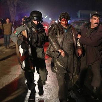 Afghan police help an injured man at the site of an explosion at a restaurant in Kabul (AP)