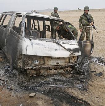 Afghan National Army soldiers investigate the site of a deadly assault by suicide bombers and gunmen against a Nato base (AP)
