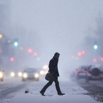 A man crosses Broad Street during a winter snowstorm in Philadelphia (AP)