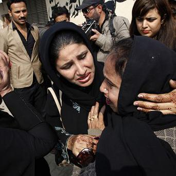 Relatives of a Pakistani polio vaccination worker, who was killed by unknown gunmen, mourn her death in Karachi (AP)