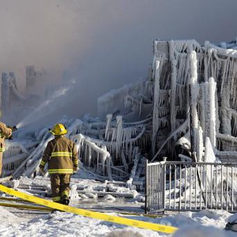 Firefighters continue to douse the rubble of a care home destroyed by fire (AP)