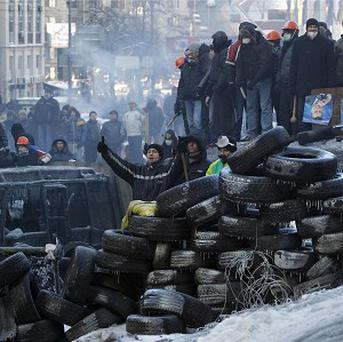 Protesters guard the barricades in front of riot police in Kiev (AP)