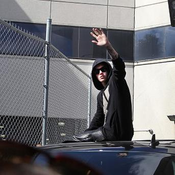Justin Bieber waves from the top of a car as he leaves the Turner Guilford Knight Correctional Centre (AP)