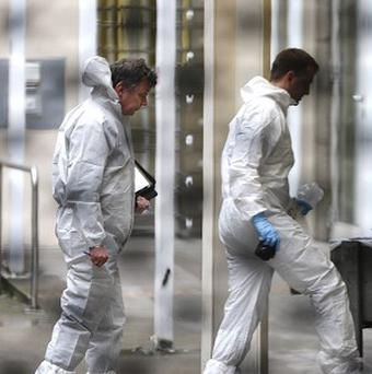 Forensic experts arrive at the scene of a shooting and stabbing incident which left two people dead in Frankfurt (AP)