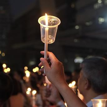 """Members of the """"White Shirt"""" movement hold up candles during a Bangkok vigil to demand democratic elections (AP)"""