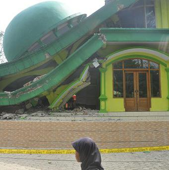 An Indonesian soldier talks on his radio near a mosque that collapsed after a 6.1-magnitude quake rocked Java island, in Banyumas, Indonesia today. Indonesia, the world's largest archipelago is prone to seismic upheaval due to its location on the so-called Pacific