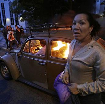 A man tries to drive his car which demonstrators set on fire amid protests against the World Cup (AP)