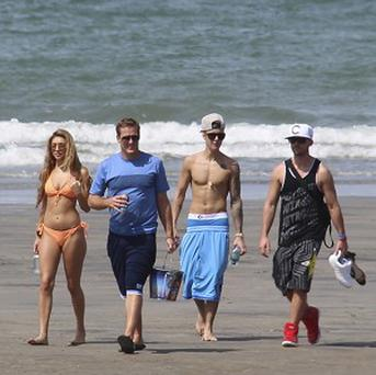 Justin Bieber, second right, and Chantel Jeffries, far left, walk with unidentified people on a beach in Panama (AP)