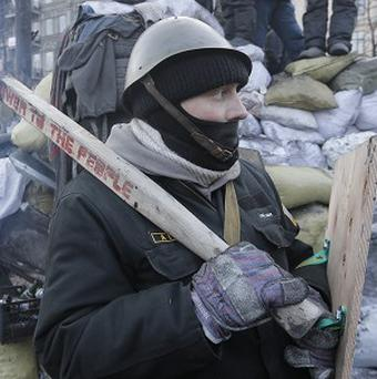 A protester stands guard at the barricades in front of riot police in Kiev (AP)