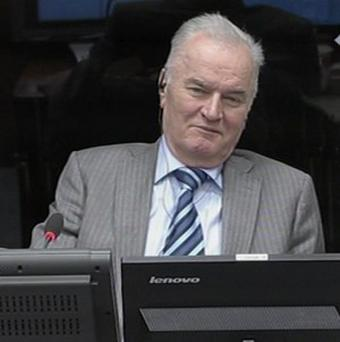 In this image taken from video former Bosnian Serb army commander Gen. Ratko Mladic smiles during his appearance at the Yugoslav war crimes tribunal Tuesday Jan. 28, 2014 in the Hague Netherlands. Mladic slammed the United Nations Yugoslav war crimes tribunal Tuesday as a satanic court and refused to testify as a defense witness for his former political master, Radovan Karadzic. A courtroom reunion of the two alleged chief architects of Serb atrocities during Bosnias 1992-95 war lasted only about an hour as Mladic repeatedly told judges he would not answer former Bosnian Serb President Karadzics questions, citing ill health and an unwillingness to risk incriminating himself. (AP Photo/ICTY, Via Associated Press Television) TV OUT