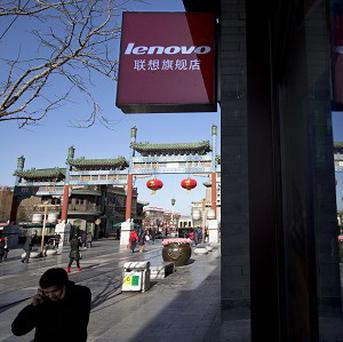 A man talks on his mobile phone as he walks past a Lenovo shop in Beijing, China. (AP)