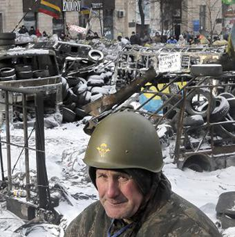 A protester guards the barricades in front of riot police in Kiev (AP)