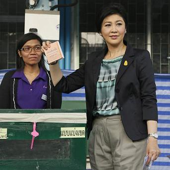Thai Prime Minister and Pheu Thai party leader Yingluck Shinawatra casts her ballot in the general election at a polling station in Bangkok. (AP)