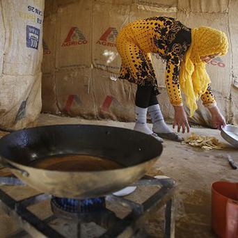 A Syrian refugee prepares food in a makeshift settlement
