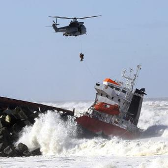 A sailor is lifted by a military helicopter after a Spanish cargo ship slammed into a jetty off Anglet, south-western France (AP)
