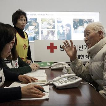 South Korean Lee Kyun-myoung, 93, talks with Red Cross members as he fills out application forms to reunite with family living in North Korea (AP)