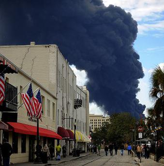 Visitor to Savannah's historic River Street watch a blaze in a warehouse at the Georgia Ports Authority Ocean Terminal (AP)