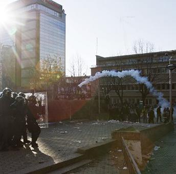 Protesters throw back a tear gas canister at Kosovo police officers guarding Pristina University (AP)