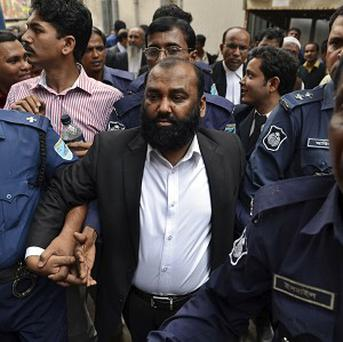 One of the two owners of Tazreen Fashions, Delwar Hossain, centre, is escorted by security personnel to a court in Dhaka, Bangladesh (AP)
