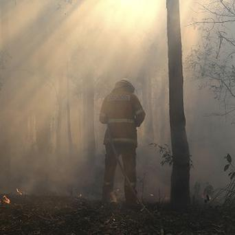 A firefighter mops up after a firestorm swept through a property in Bilpin (AP)
