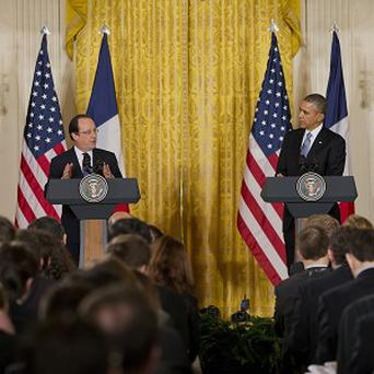 Barack Obama listens as French president Francois Hollande speaks during their joint news conference in the East Room of the White House (AP)