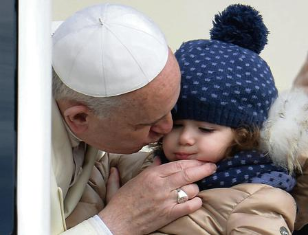 Pope Francis kisses a child as he arrives to lead the General Audience in Saint Peter's Square at the Vatican