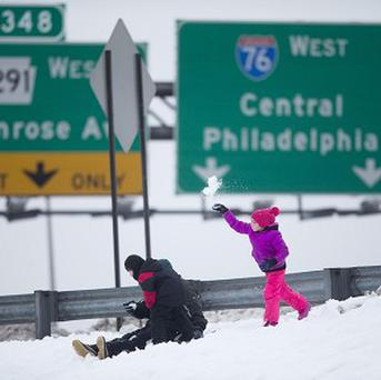 A young girl tosses snow from an Interstate 76 embankment as she and others play in Philadelphia (AP)