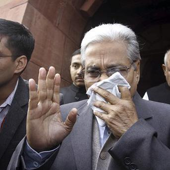 An Indian MP covers his face with a handkerchief after being affected by pepper spray in parliament (AP)
