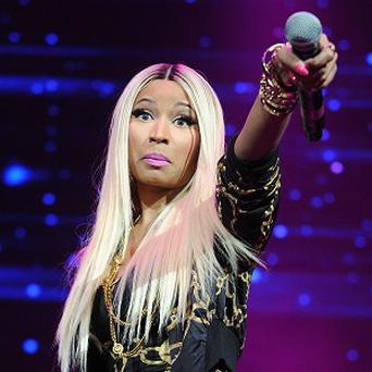 Nicki Minaj has been criticised for using a photo of Malcolm X with a gun in his hands, juxtaposed with a racial slur, for her new single (Invision/AP)