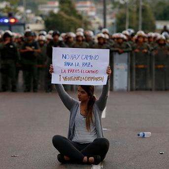 A demonstrator holds up a sign that reads 'There is no road to peace. Peace is the way. Awake Venezuela' in front of National Bolivarian Guards in riot gear (AP)