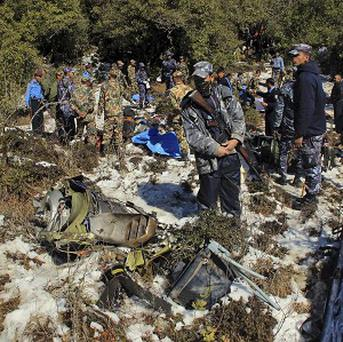 Nepalese police officers and army soldiers inspect the wreckage of a Nepal Airlines plane that crashed at Khachikot in Argakhanchi district in western Nepal (AP)