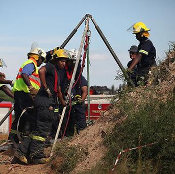 Emergency rescue workers attempt to free trapped miners at a disused gold mine shaft near, Benoni, South Africa (AP)