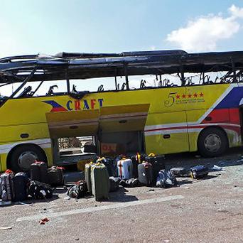 A policeman stands guard in front of a damaged bus after a deadly explosion in Taba (AP)