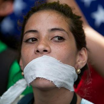 A demonstrator covers her mouth with a rag to protest against government censorship, during a march in Caracas (AP)