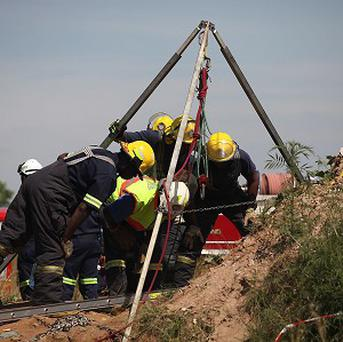 Emergency rescue workers attempt to free trapped illegal miners at a disused gold mine shaft near Benoni, South Africa (AP)